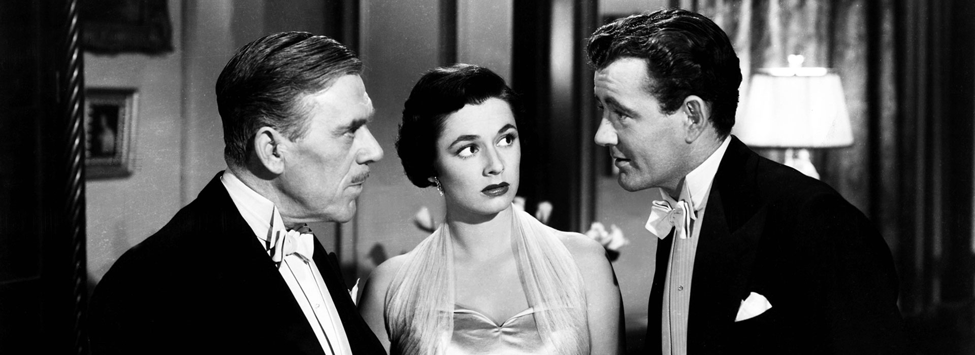 Bruno Anthony (Robert Walker, re.) irritiert Senator Morton (Leo G. Carroll, li.) und seine Tochter Anne (Ruth Roman, Mi.) mit bizarrem Small Talk.